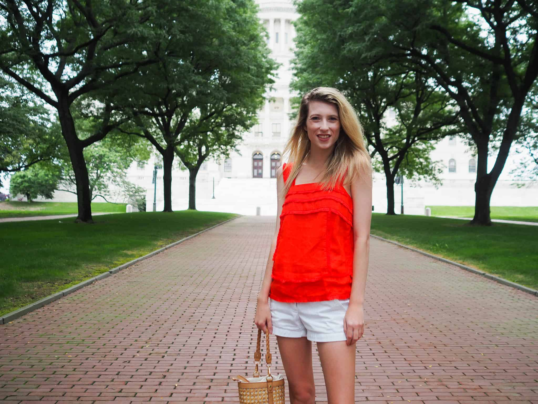 A red linen top with tassel trim detail for a spicy look. Paired with white chino shorts and a straw bag. A complete summer ensemble. Shop my look links below!